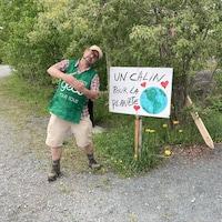 Maurice Duclos est à côté d'une pancarte avec un dessin de la planète Terre où il est écrit  «Un câlin pour la planète»,