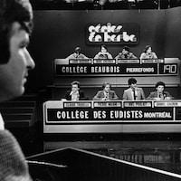 Dans un studio de télévision, l'animateur Michel Benoît fait face aux quatre participants du collège Beaubois de Pierrefonds et à ceux du Collège des Eudistes de Montréal.