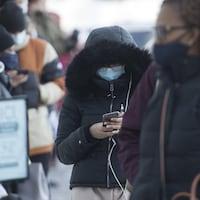 Des gens portant un masque font la file à l'extérieur d'un commerce.