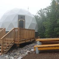 Un géodôme, une sorte de tente sphérique, dans le brouillard.