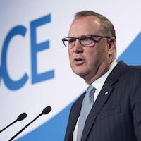 George Cope parle au micro devant un logo de BCE.