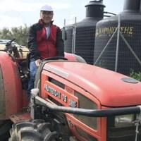 George Pananos sur un tracteur à l'oliveraie.