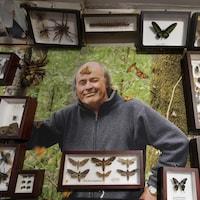 Une photo de Georges Brossard est cernée de cadres contenant aussi bien des papillons que des scarabées ou une tarentule.