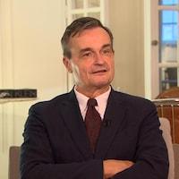 Un homme en complet veston et cravate répond aux questions d'un journaliste.