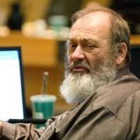 Le conseiller municipal de Sudbury Gerry Montpellier, assis à la table du conseil municipal devant un ordinateur.