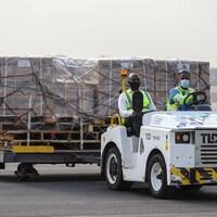 Deux hommes transportent des boîtes de doses de vaccins à bord d'un véhicule sur le tarmac.