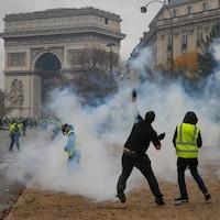 Des manifestants des « gilets jaunes », enfumés de gaz lacrymogènes, lancent des projectiles près de l'Arc de triomphe à Paris.
