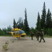 Des hommes en tenue militaire s'apprêtent à monter dans un hélicoptère.