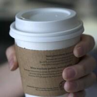Photo d'une main qui tient un gobelet de café en carton.