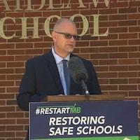 Le ministre de l'Éducation Kelvin Goertzen, au pupitre devant une école.