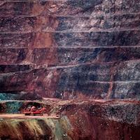 Une petite grue rouge tranche sur l'immensité de la mine.