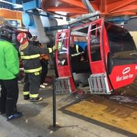 Une gondole rouge portant le logo du Mont-Sainte-Anne est inspectée par le service d'incendie.