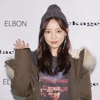 Une jeune femme porte une tuque et fait un signe de salutation à la caméra.