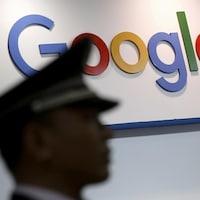 La silhouette floue de profil d'un homme aux traits asiatiques portant une casquette de policier devant le logo de Google.