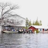 Des gens sur deux canots à moteur devant des maisons inondées.