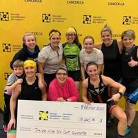 Des femmes posent dans des vêtements de cyclisme, tenant un chèque géant au profit de la Société canadienne du cancer.