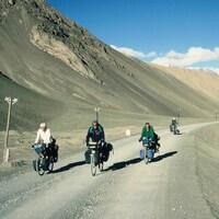 Quatre personnes à vélo sur une route montagneuse.