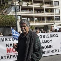 Un manifestant garde un drapeau grec lors d'une manifestation devant des dizaines d'autres manifestants qui tiennent une banderole.