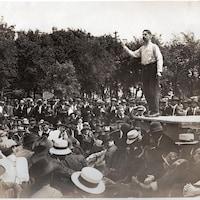 Un homme debout sur une estrade parle à une foule.