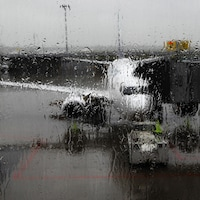 Un avion est vu à travers une fenêtre couverte de pluie à l'aéroport Montréal-Trudeau.
