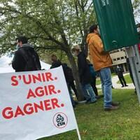 Un petit drapeau sur lequel est écrit : S'unir, agir, gagner. Des grévistes sont derrière.