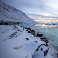 Village sur le bord de la rive d'une mer glacée.