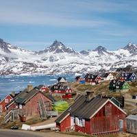 De petites maisons multicolores sont dispersées dans une baie avec en toile de fond des montagnes enneigées.