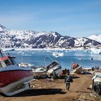 Un paysage du Groenland où l'on retrouve des bateaux, une étendue d'eau et des montagnes.
