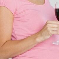 Une femme enceinte, un verre de vin rouge à la main