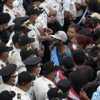 Un groupe de personnes face à des hommes en uniforme