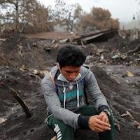Un homme qui fouille les décombres après l'éruption du volcan de Fuego prend une pause. Le sol est ravagé et les bâtisses en arrière-plan sont démolies.