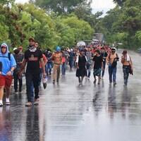 Des migrants marchent sur une route asphaltée.