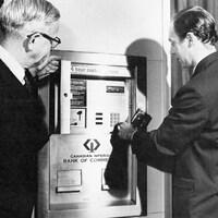 Deux hommes en train d'utiliser un des premiers guichets automatiques de la Banque CIBC.
