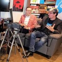 Quatre hommes discutant sur des sofas entourés. Des appareils électroniques, des jeux de société et des jeux vidéo occupent une bonne partie de l'espace et des étagères les entourant.