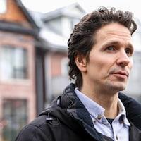 Un homme aux cheveux courts ondulés bruns et aux yeux bleus devant une maison.