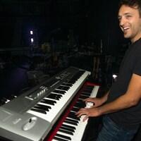 Guillaume Marchand souriant, les doigts sur un clavier.