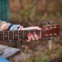 Une musicienne joue de la guitare dans un parc.