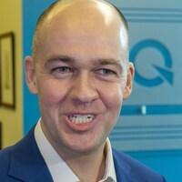 Guy Nantel devant le logo du Parti québécois.