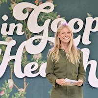 Gwyneth Platrow sur une scène. Elle tient des cartons dans ses mains. Derrière elle apparaît en grosses lettres le nom de l'événement.