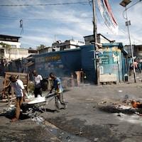 Trois hommes passent avec une brouette dans une rue remplie de déchets.