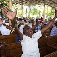 Des gens lèvent les bras et prient.