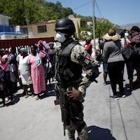 Un agent de police surveille une file tout en portant un masque.