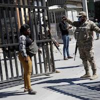 Un membre des forces armées discute avec une femme devant une clôture.