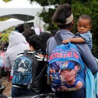 """Un petit garçon aux bras de sa maman qui soutient un sac à dos """"Never give up"""" dans une file"""