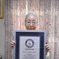 Une femme âgée tient un certificat de l'organisation des records Guinness.