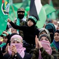 Des partisans du Hamas, certains masqués, sont rassemblés et portent des drapeaux verts.