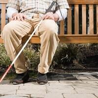 Un homme handicapé visuel assis sur un banc avec sa canne blanche.
