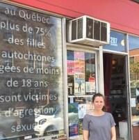 Hannah Claus devant la vitrine du magasin Phonopolis sur laquelle est inscrite une statistique concernant la proportion de femmes autochtones victimes d'agression sexuelle.