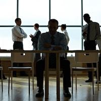 Une personne assise à une table dans une salle de réunion avec un groupe d'autres personnes derrière elle.