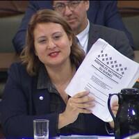 Catherine Harel-Bourdon assise tient dans ses mains une copie du projet de loi 40.